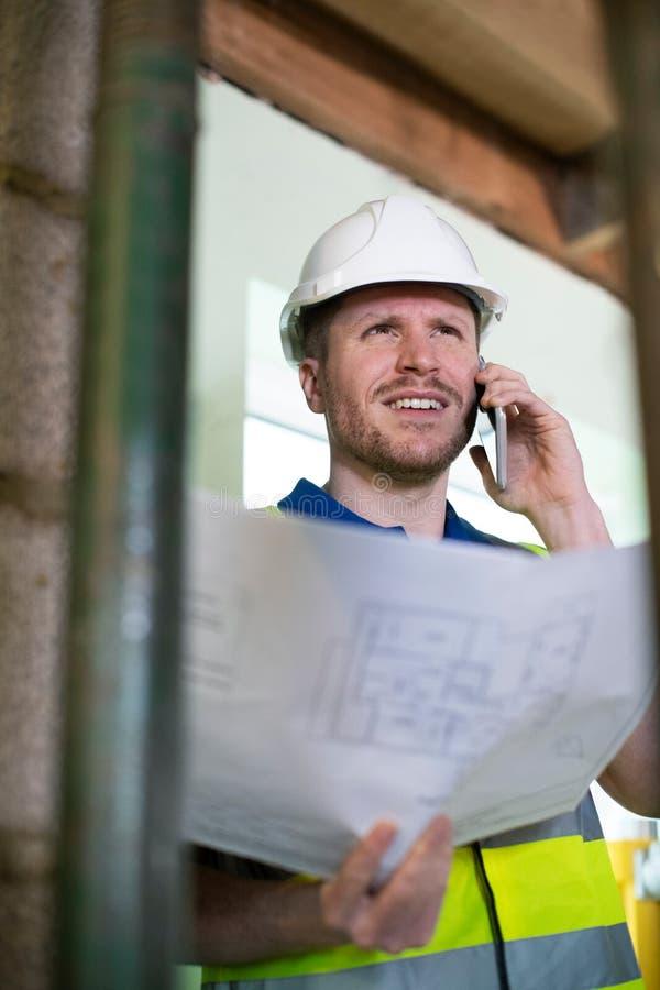 Architekt Inside House Being erneuerte das Studieren von Plänen sprechend am Handy stockfotografie