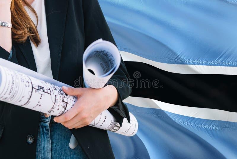 Architekt kobiety mienia projekt przeciw Botswana falowania flagi tłu Budowy i architektury poj?cie fotografia stock