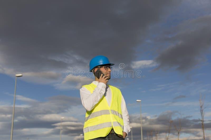 Architekt lub Inżynier rozmawiający na swoim telefonie komórkowym na budowie Koncepcja zadania Ubrania ochronne zdjęcia royalty free