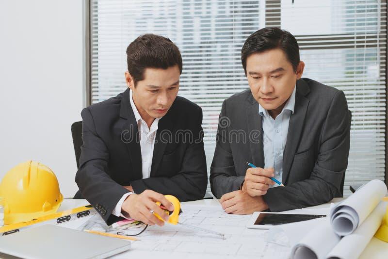 Architekt oder Immobilienagentur, die Arbeit mit Plänen besprechen lizenzfreies stockbild