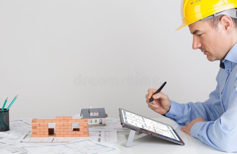 Architekt używa cyfrową pastylkę na biuro stołu biurku obrazy stock