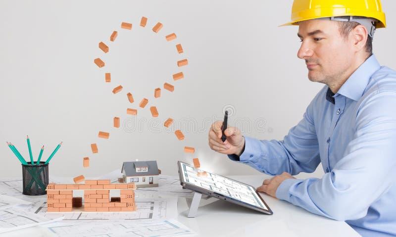 Architekt używa magiczną cyfrową pastylkę i budujący model domową budowę zdjęcia stock