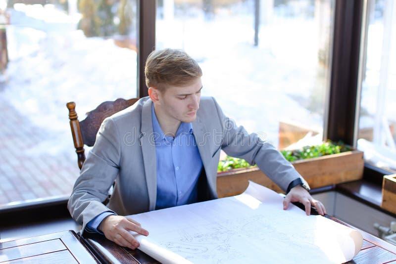 Architekta czekanie dla klienta przy kawiarnią z rolki architektury pr obraz stock