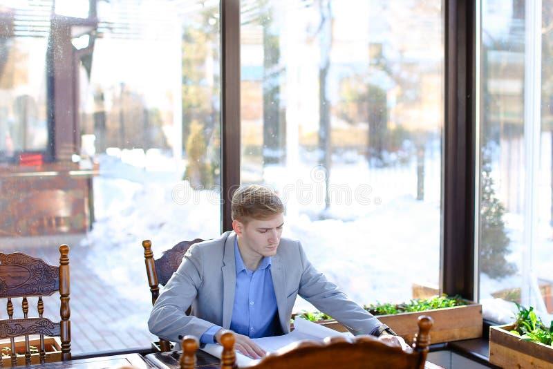 Architekta czekanie dla klienta przy kawiarnią z rolki architektury pr obrazy stock
