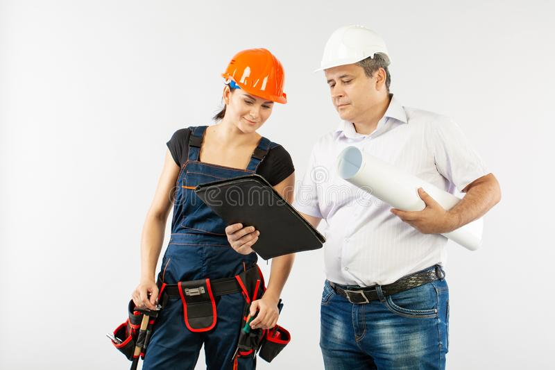 Architekta mężczyzna jest ubranym ciężkiego kapeluszu lub budowniczego kobiety przegląda projekty hełma i współpracownika zdjęcie royalty free