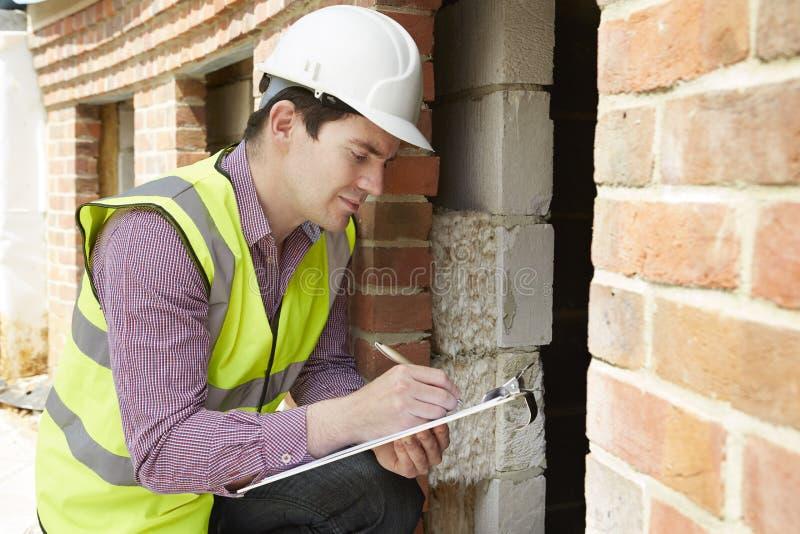 Architekten-Checking Insulation During-Haus-Bau lizenzfreies stockbild