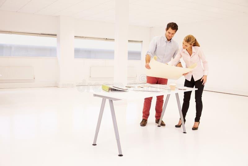 Architekten, die Plan von leeren Büroräumen planen lizenzfreie stockbilder