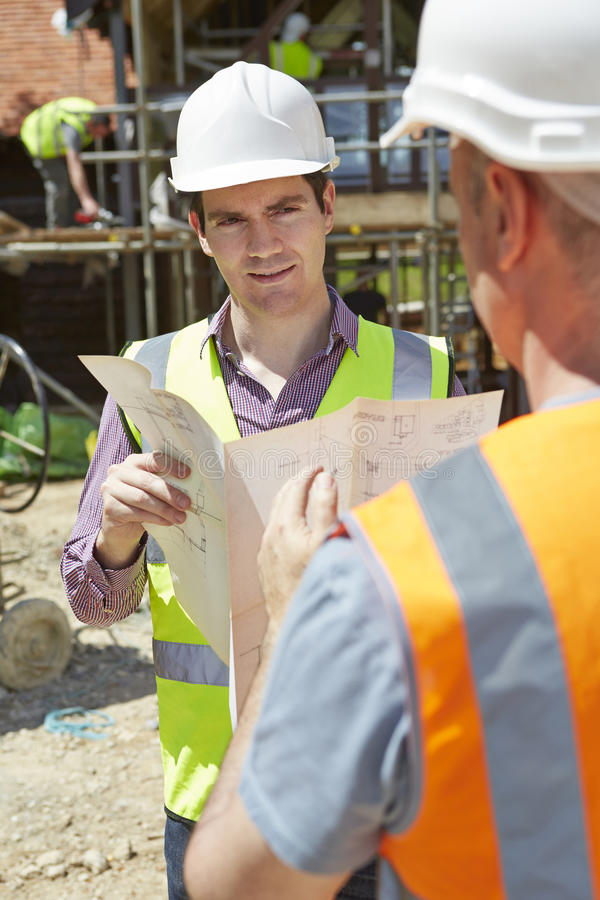 Architekten-Discussing Plans With-Erbauer On Construction Site stockbild