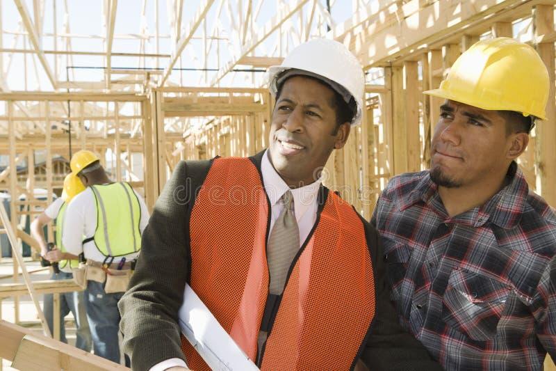 Architekten-With Foreman Inspecting-Rahmen lizenzfreies stockbild