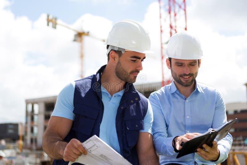 Architekten- und Arbeitskraftplanungssitzung auf Baustelle lizenzfreies stockfoto