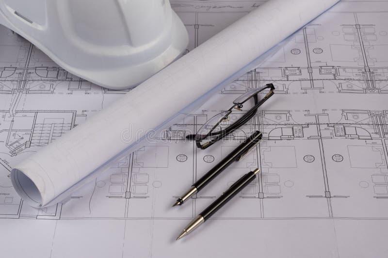 Architektenarbeitsplatz - Architekturpläne mit messendem Band, Schutzhelm, Gläsern und antreibendem Bleistift auf Tabelle Spitze  lizenzfreie stockfotos