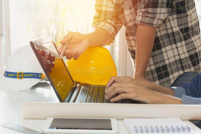 Architekteningenieur, der Laptop für das Arbeiten mit gelbem Sturzhelm a verwendet lizenzfreie stockfotos