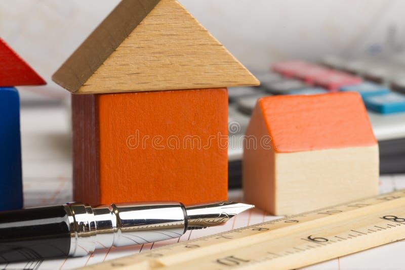 Architektoniczny projekt nowy dom z drewnianym modela domem, kalkulatorem i planami na stole, obrazy stock