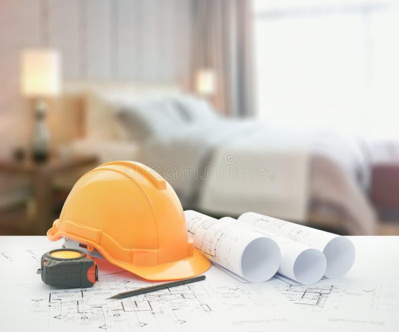 Architekturplan mit Schutzhelm und Werkzeuge über modernem Schlafzimmer mit dekorativer Lampe als Hintergrund stockfotos