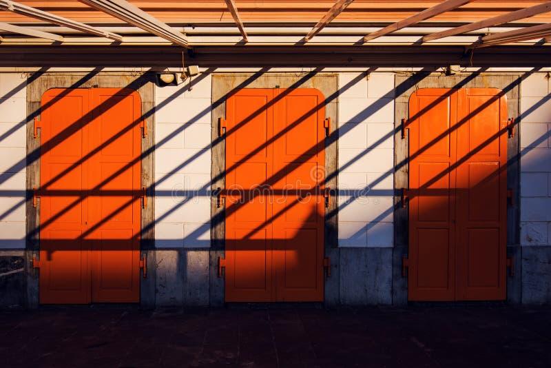 Architektury abstrakcjonistyczny tło, trzy pomarańczowego drzwi i cienie, zdjęcia royalty free