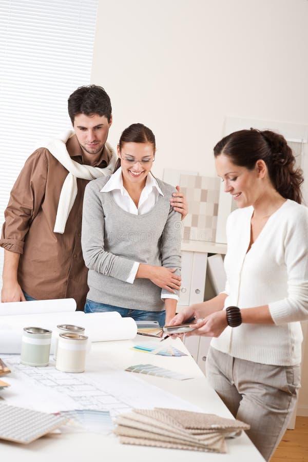 Architetto arredatore femminile con due clienti fotografia stock