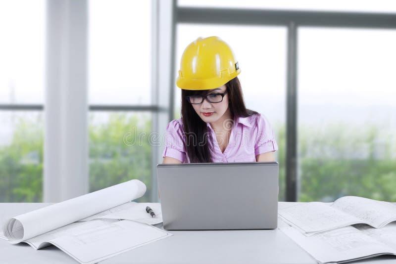 Architetto asiatico che utilizza computer portatile nell'ufficio immagini stock libere da diritti
