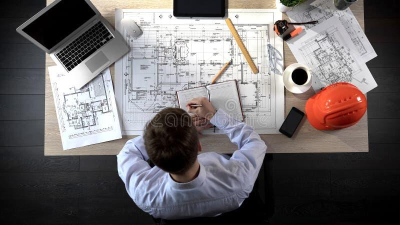 Architetto che controlla disegno della costruzione, facente le note per discutere con i colleghi immagini stock