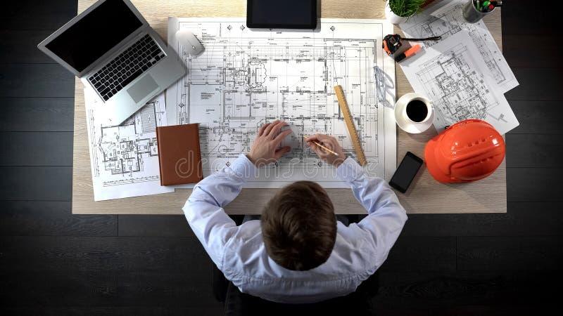Architetto che fa i segni supplementari, uscite di sicurezza di disegno nel caso dell'evacuazione immagine stock