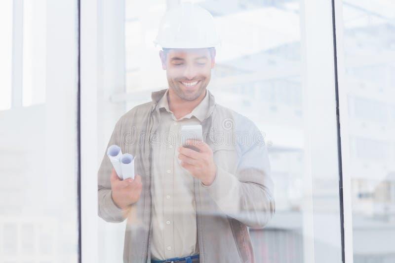 Architetto che utilizza telefono cellulare nell'ufficio immagini stock