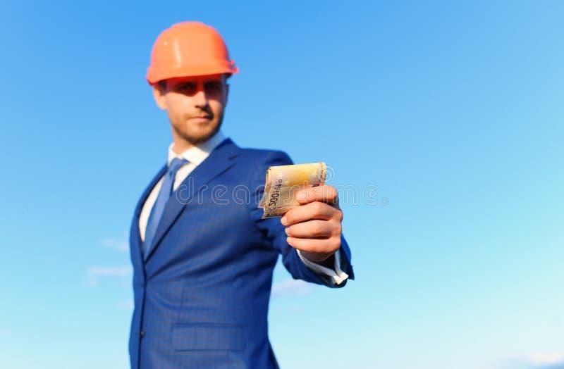 Architetto con il fronte sorridente nei contanti di elasticità del casco e del vestito immagine stock libera da diritti