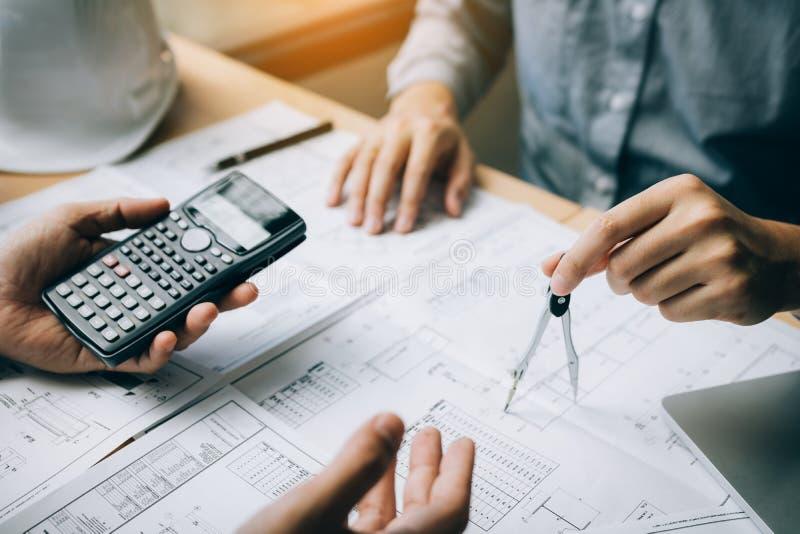 Architetto due che lavorano al cantiere e disegno della bussola che indica sul modello con il calcolatore per calcolare immagini stock libere da diritti