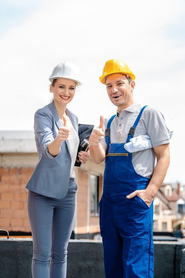 Architetto e muratore sul sito che d? il pollice in su fotografia stock libera da diritti