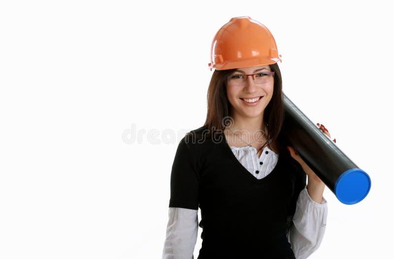Architetto felice della donna con l'elmetto protettivo ed il tubo arancioni fotografia stock