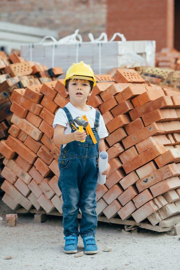 Architetto nel casco a scrivere qualcosa vicino a un nuovo edificio piccolo ragazzo carino nell'edificio come architetto fotografie stock