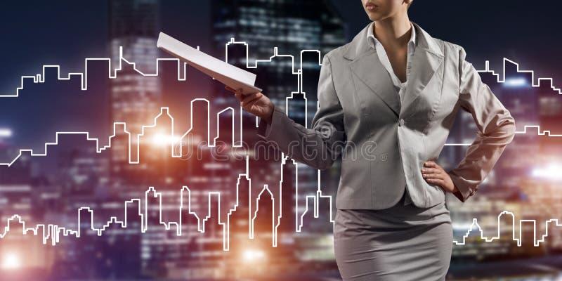 Architetto o ingegnere della donna che presenta concetto della costruzione e che giudica i documenti disponibili illustrazione di stock