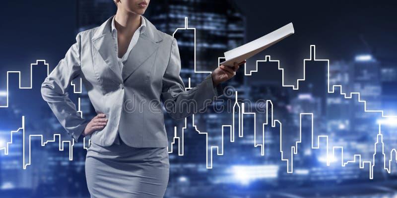 Architetto o ingegnere della donna che presenta concetto della costruzione e che giudica i documenti disponibili immagine stock