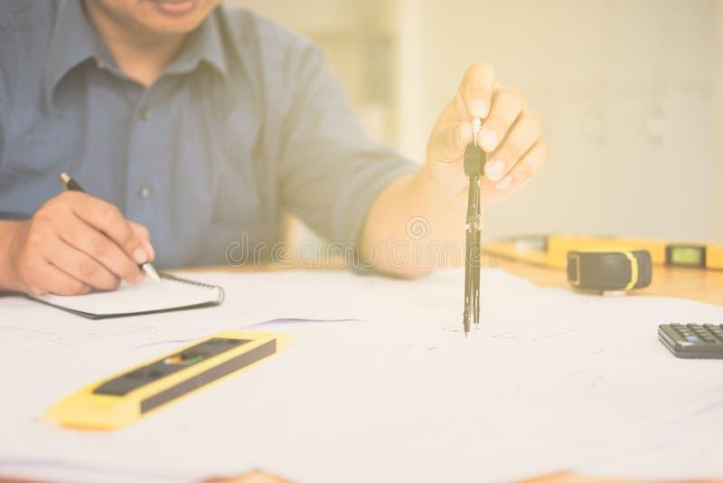 Architetto o pianificatore che lavora ai disegni per costruzione fotografia stock