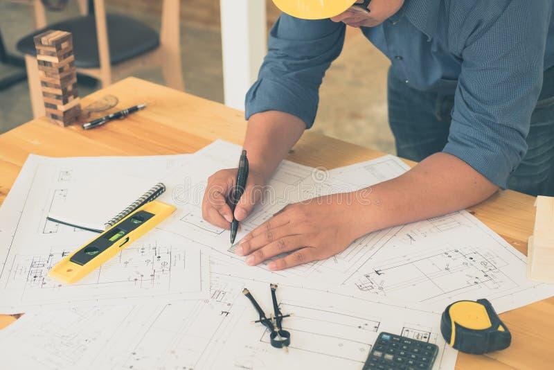 Architetto o pianificatore che lavora ai disegni per costruzione fotografie stock libere da diritti
