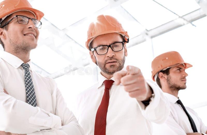 Architetto sicuro in un casco protettivo che indica voi immagine stock
