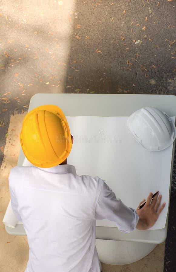 Architetto Working On Blueprint costruisca l'ispettore in posto di lavoro, la vista dell'angolo alto, modello fotografie stock libere da diritti
