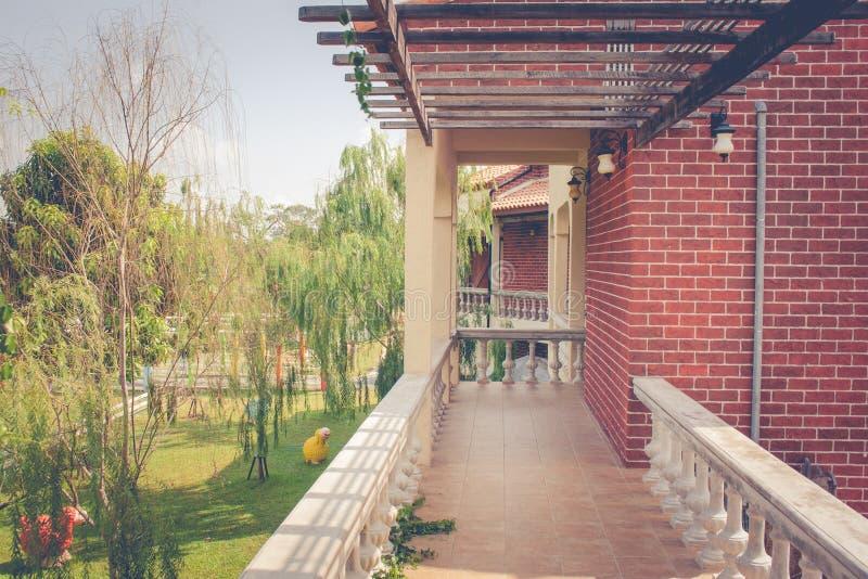 Architettura della via o del passaggio pedonale sul secondo piano di vecchie costruzioni di mattone d'annata accanto al giardino  immagine stock libera da diritti