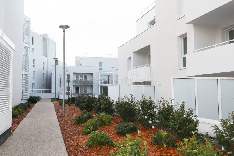 Architettura di costruzione moderna della proprietà con il giardino nella proprietà bianca fotografie stock