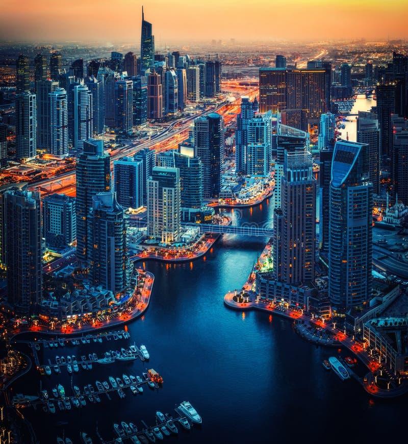 Architettura illuminata del porticciolo del Dubai di notte Orizzonte blu scenico di ora immagine stock