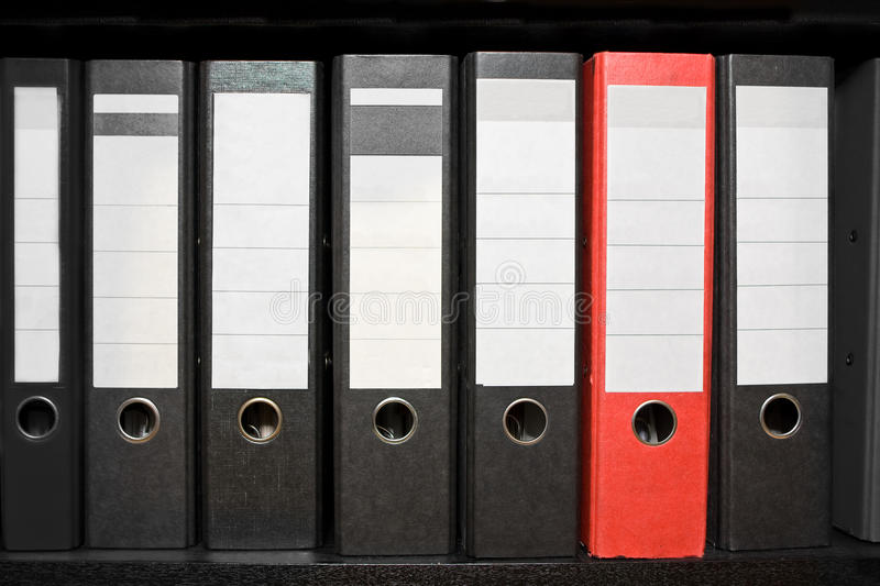 Archive folder. Row of black archive folders with one red folder stock photos