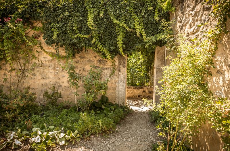Archway gate and historic stone wall in the garden nook. Archway gate, historic stone wall and climbing plants in the mysterious garden nook - landscape stock photography
