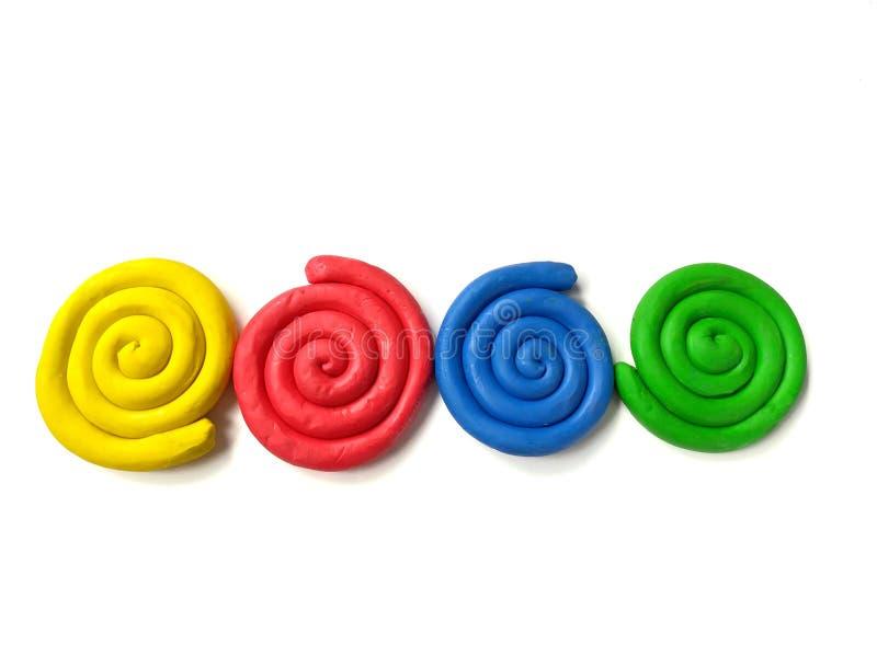 Arcilla colorida del plasticine, pasta espiral de la forma, fondo blanco foto de archivo libre de regalías
