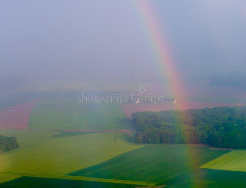 Arco-íris brilhante sobre o campo agrícola fotos de stock