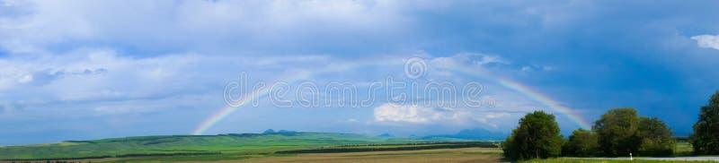 Arco-íris com as nuvens sobre o campo de exploração agrícola imagens de stock