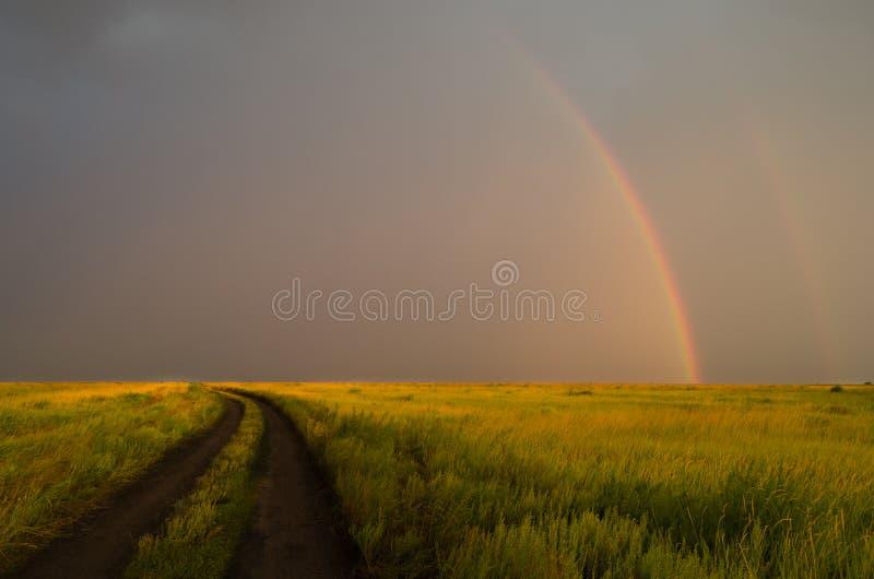 Arco-íris dobro após a chuva no fundo de nuvens de tempestade Estrada no campo imagem de stock royalty free