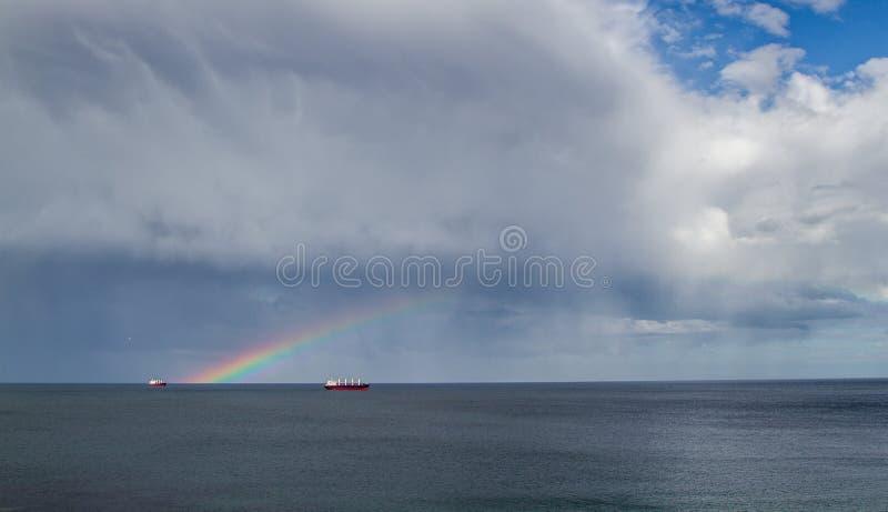 Arco-íris dobro para fora no mar sobre alguns barcos imagens de stock