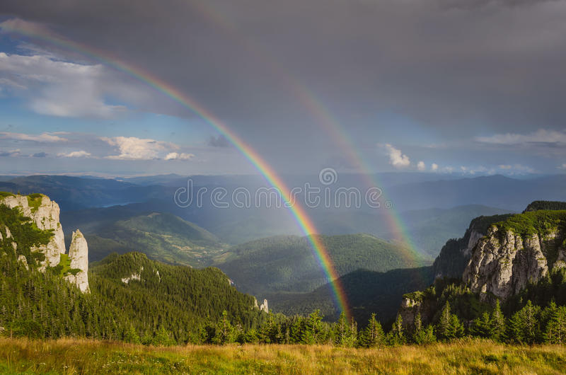 Arco-íris dobro sobre as montanhas imagens de stock