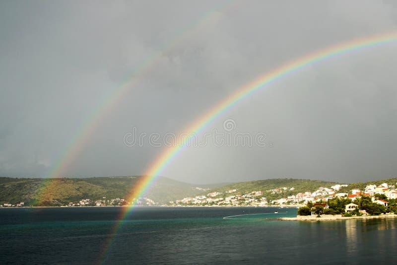 Arco-íris dobro sobre a cidade pequena foto de stock