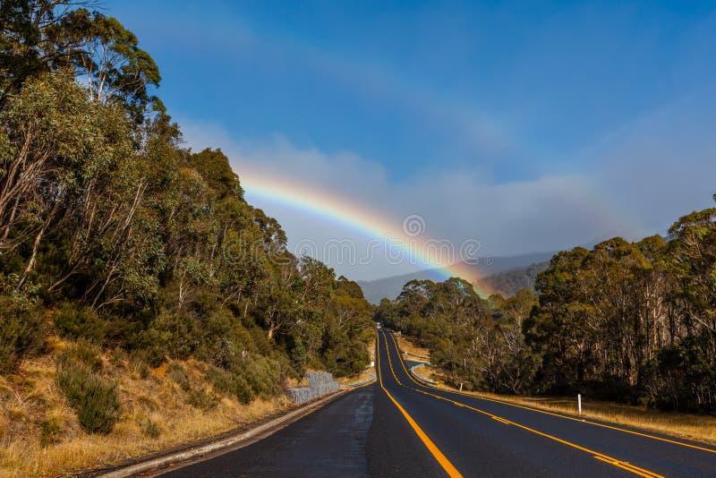 Arco-íris dobro sobre a estrada e a floresta da montanha foto de stock royalty free