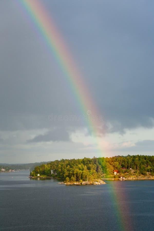 Arco-íris na chuva durante a luz do sol no mar imagens de stock royalty free