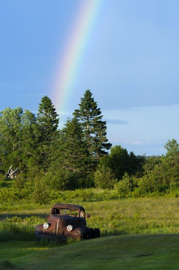 Arco-íris pelo caminhão velho em Maine Field fotografia de stock royalty free